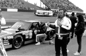 Dr. Jerry Punch provides commentary from track level in 1988 at North Carolina Motor Speedway. Behind him sits Dale Earnhardt in his car. (Keith Payne/ESPN)